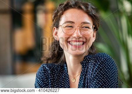 Portrait of laughing young woman wearing spectacles in office. Carefree casual girl wearing glasses and looking away. Confident beautiful student wearing specs and smiling.