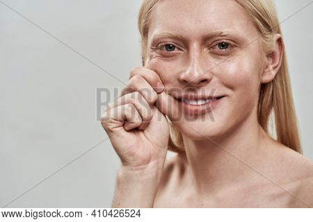 Groomed Young Caucasian Man With Long Fair Hair Tightening His Cheek And Smiling At Camera While Pos