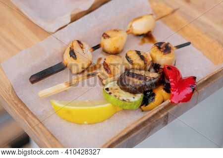 Cooked Scallop Meat Skewers In Paper Take Out Box At Summer Local Food Market - Close Up. Outdoor Co