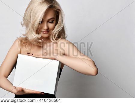 Portrait Of Young Positive Pretty Blonde Woman Standing And Holding White Paper Shites Or Empty Box