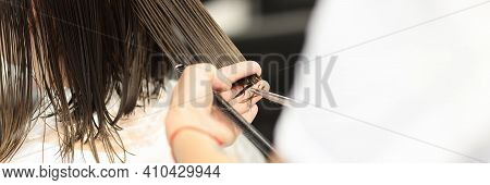 Hairdresser Holds Clients Wet Hair And Cuts It. Training Profession Hairdresser Concept