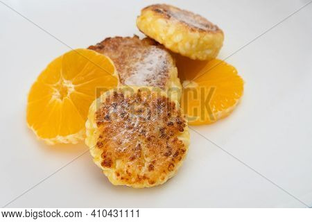 Three Sweet Curd Cottage Cheese Pancake Sprinkled With Powdered Sugar With Two Orange Slices Close-u