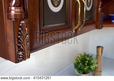 Selective Focus Fragment Of Cherry Alder Wooden Cabinetry Kitchen Carved Detail. Carved Decorative D