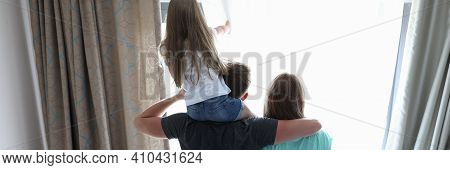 Family Dad Mom Daughter Stand With Their Backs Hugged And Look Out Window. Mutual Understanding And