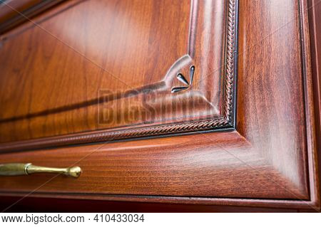Selective Focus Fragment Of Cherry Alder Wooden Cabinetry Kitchen Carved Detail. Wooden Pilasters. D