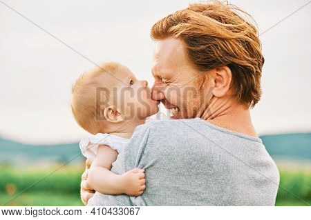 Adorable Baby Biting Nose Of Her Father, Young Family Man Playing Outside Wth Little Kid
