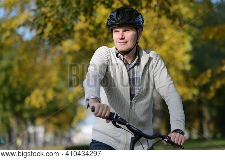 Portrait of a pensive mature Caucasian man in casual clothing and bike helmet on his city bicycle looking away in an autumn city park