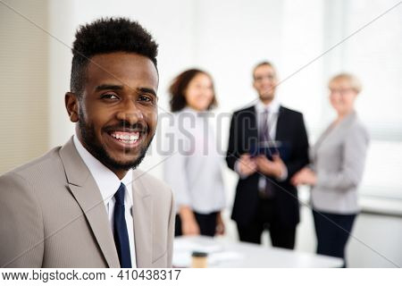 Portrait of young african-american businessman and his colleagues on the background at the office