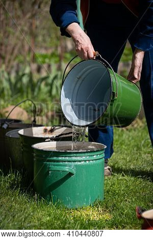 Grandmother Pours Water From A Bucket Into A Basin. Many Different Buckets Stand In A Row To Collect
