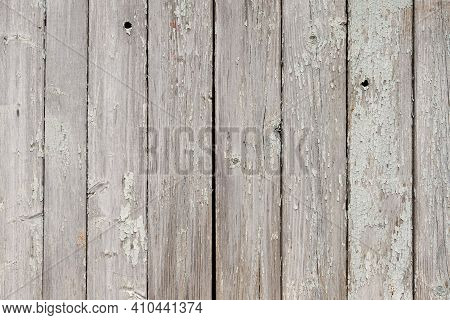 Part Of An Old Fence Of Painted Wooden Boards On The Street. Old Wooden Fence Made Of Flat Boards. F