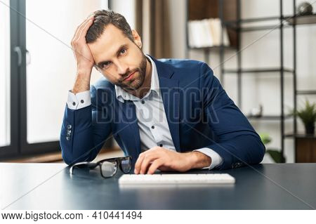 Helpless Unlucky Young Handsome Businessman With Beard Sitting At The Desk With One Hand On Keyboard