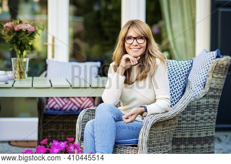 Portrait Of Middle Aged Attractive Woman Looking At Camera And Smiling While Relaxing At The Balcony