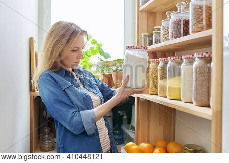 Middle Aged Woman At Home In Kitchen In Pantry, Female Looking At Food On Wooden Storage Shelves Hol