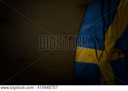 Nice Dark Picture Of Sweden Flag With Big Folds On Dark Wood With Free Space For Your Text - Any Hol