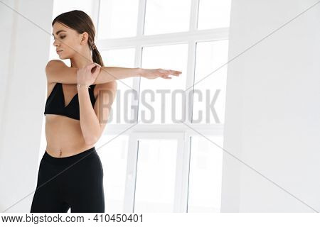 Athletic young sportswoman stretching her arm while working out indoors