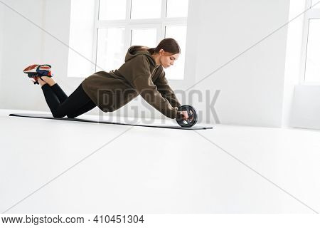 Athletic young sportswoman doing push-ups with equipment while working out on mat indoors