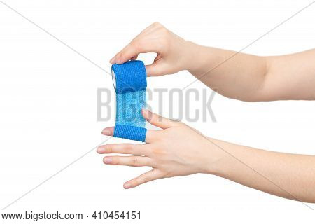 Man Winds An Elastic Bandage On His Hand On A White Background, Isolate. The Concept Of Fixation Of