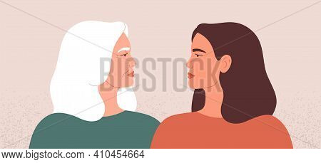 Two Strong Women Look At Each Other. Side View Of Mature Mother And Her Young Daughter Stand Togethe