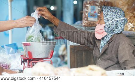 Yogyakarta, Indonesia. February 28, 2021: An Old Woman With A Mask On Her Face Is Selling Her Wares