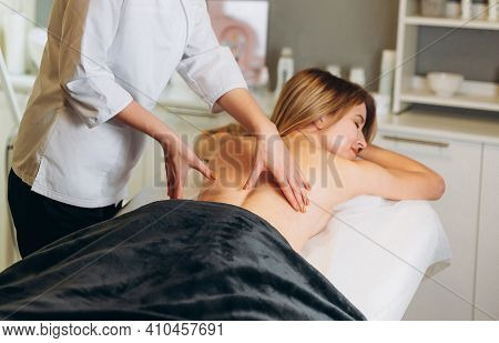 Young Woman During Spa Salon. Woman Relaxes In The Spa. Spa Body Massage Woman Hands Treatment. Woma