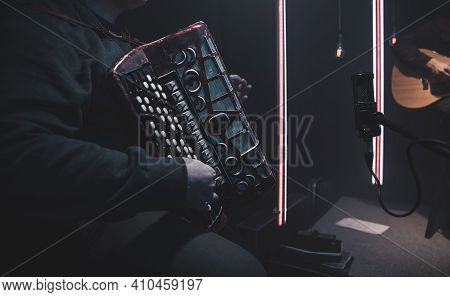 The Musician Plays The Accordion In The Studio With Musicians. The Concept Of Music Recording Or Mus