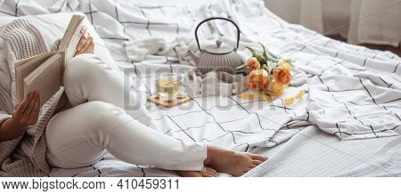 Woman Reads A Book In Bed With Tea And Bouquet Of Tulips. Spring Morning And Weekend Concept.