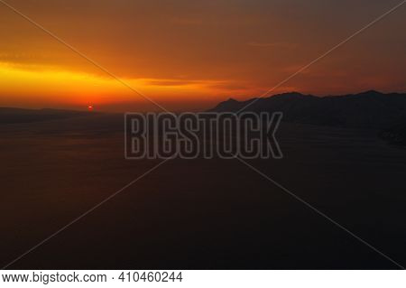 Beautiful Sunset View At The Seacoast. Splendid Red And Orange Sky, Mountain Silhouettes, Endless Se