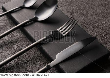 Black Matte Cutlery Set-fork, Spoon, Knife, On Dark Wood. Minimalistic Still Life, Stylish Tableware