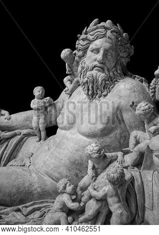 Ancient bust of Nile river god. Head and shoulders detail of the ancient man with beard sculpture. Antique statue isolated on black background