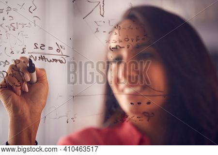 Brainstorming Businesswoman Or Mathematician Drawing Graph Calculation On Glass Screen In Office
