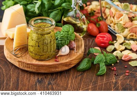 Jar With Homemade Pesto Sauce On Rustic Background With Parmesan Cheese, Olive Oil, Sause Pesto, Bas