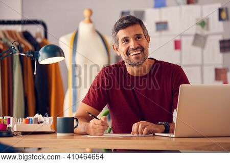Portrait Of Male Fashion Designer In Studio Working On Sketches Or Documents At Desk With Laptop