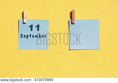 11 September. 11th Day Of The Month, Calendar Date. Two Blue Sheets For Writing On A Yellow Backgrou