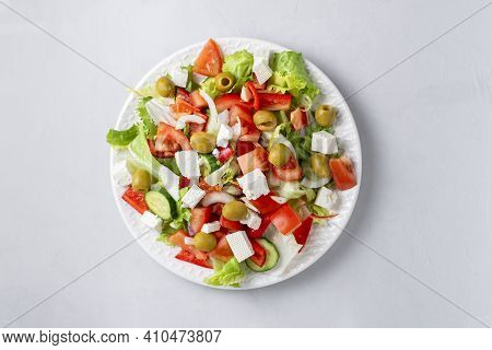 Delicious Vegetable Greek Salad With Feta, Tomatoes, Olives, Greens On Light Background. Served With