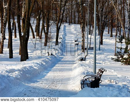 Winter Park, Wooden Benches In Snowdrifts Along A Cleared Path In The Snow In A Park On A Sunny Day.