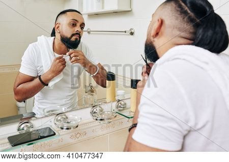 Stylish Serious Man Standing At Bathroom Mirror And Cutting Beard With Small Scissors