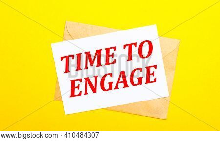 On A Yellow Background, An Envelope And A Card With The Text Time To Engage. View From Above