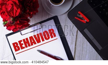 The Word Behavior Is Written In Red On A White Notepad Near A Laptop, Coffee, Red Roses And A Pen