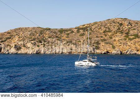 Ios, Greece - September 26, 2020: Catamaran Sailing On Aegean Sea Near Ios Island In Greece.