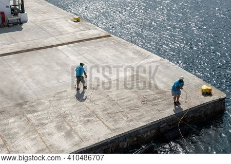 Ios, Greece - September 26, 2020: Harbor Workers With Rope In The Port Of Ios. Cyclades, Greece