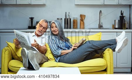 Senior Man Pointing At Newspaper Near Asian Wife Sitting On Sofa With Book