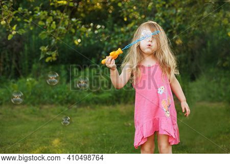 Cute Little Girl Is Blowing Soap Bubbles