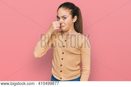 Beautiful brunette little girl wearing casual sweater smelling something stinky and disgusting, intolerable smell, holding breath with fingers on nose. bad smell