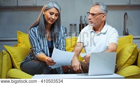 Elderly Interracial Couple Holding Papers While Sitting Near Laptop