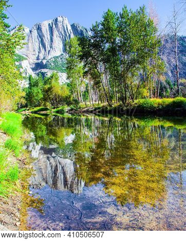 Charming little lake in the Yosemite Valley. Yosemite Park is located on the slopes of the Sierra Nevada. The rock-monolith El Capitan is reflected in the smooth water