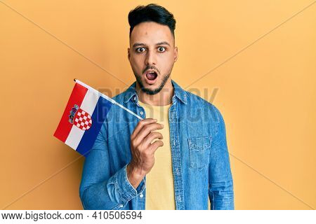 Young arab man holding croatia flag scared and amazed with open mouth for surprise, disbelief face