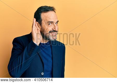 Middle age hispanic man wearing business clothes smiling with hand over ear listening and hearing to rumor or gossip. deafness concept.