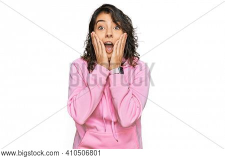Young hispanic woman wearing casual sweatshirt afraid and shocked, surprise and amazed expression with hands on face
