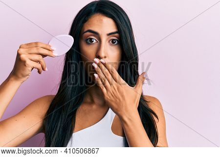 Beautiful hispanic woman holding makeup sponge covering mouth with hand, shocked and afraid for mistake. surprised expression