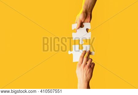 Closeup Hands Of Man Connecting Jigsaw Puzzle. Two Hands Trying To Connect Couple Puzzle With Yellow